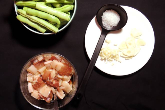 Home Cooking Recipe: 1 Wash the slices of pork belly, put a proper amount of oil, soy sauce, cooking wine for about 20 minutes. 2 Slice 2 pieces of garlic, 1 slice of garlic and cut 3 grains of green beans, wash, cut half 4, burn a pot of water.
