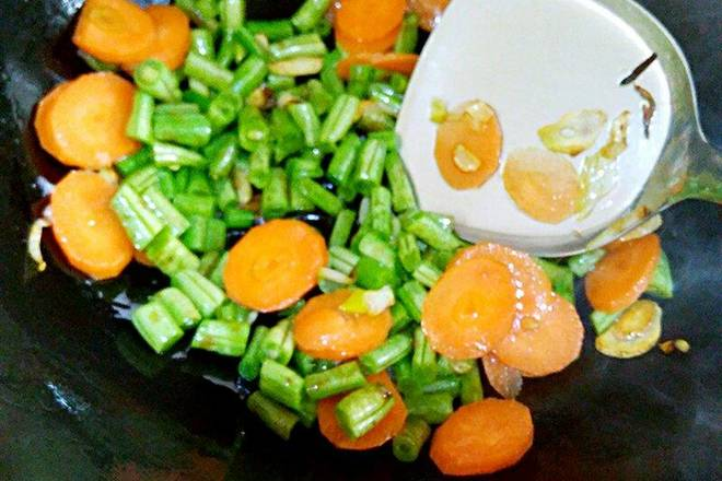 Home Cooking Recipe: A little vegetable oil, onion garlic casserole, add carrots and beans for a minute, add soy sauce.