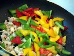Home Cooking Recipe: After a minute, pour in the colored peppers and bell peppers. Add the salt and stir fry for 2 minutes.
