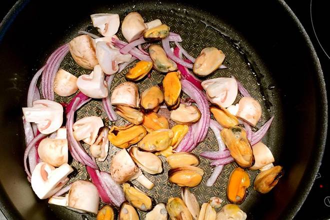 Home Cooking Recipe: After the onion is fried, add the mussels and the mushrooms.