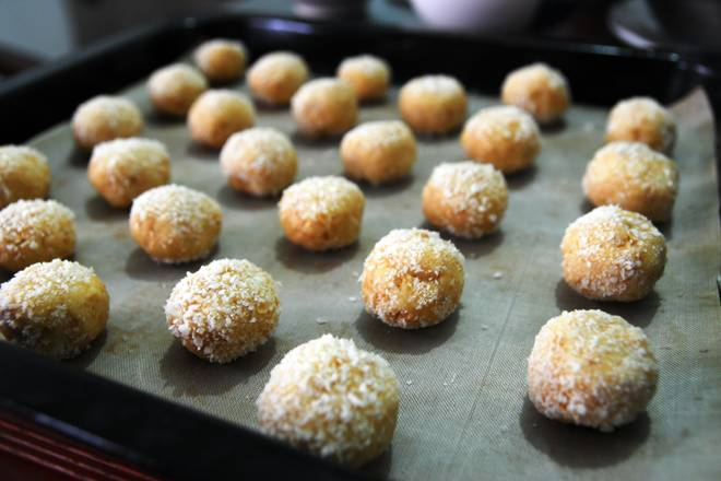 Home Cooking Recipe: Divide the dough evenly, knead it into small balls, roll it on the remaining coconut, and place it in the baking tray
