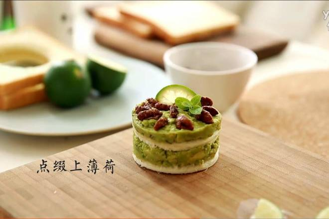 Home Cooking Recipe: First spread a layer of avocado on the bottom of a piece of toast, then cover the bottom of the second toast, then layer a layer of avocado, and finally put the nuts evenly, with lemon slices and mint leaves.