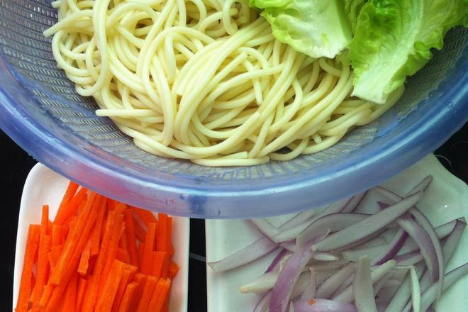 Home Cooking Recipe: Pasta cooked and simmered on the cold water, then drained and drained. Carrots and onions are washed and shredded, and the lettuce is washed and ready for use.