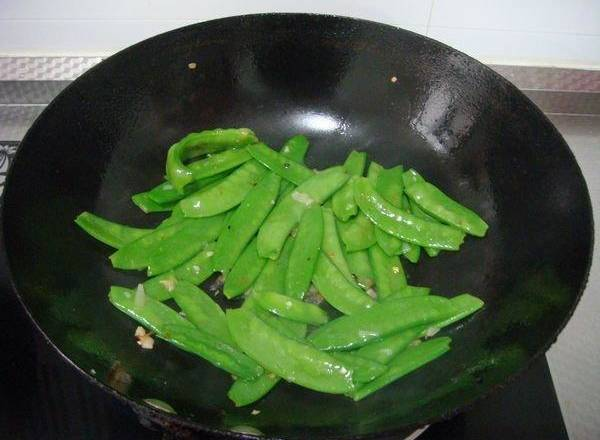Home Cooking Recipe: Pour in the peas and continue to stir fry.