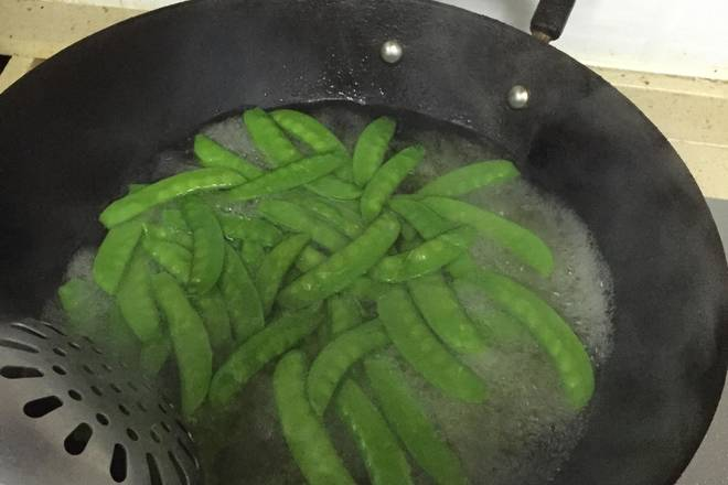 Home Cooking Recipe: Pour the right amount of water into the pan, add a spoonful of salt and the right amount of vegetable oil, then boil, add the peas, simmer for half a minute, and remove.