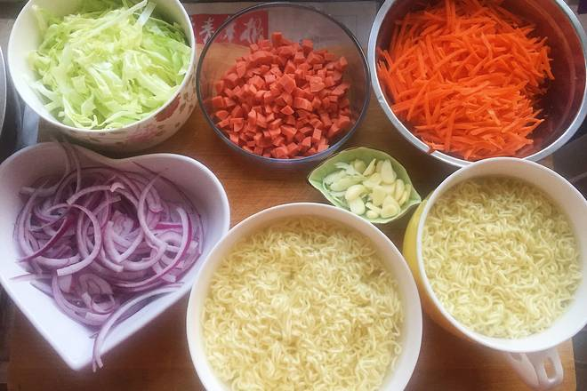 Home Cooking Recipe: Prepare the ingredients, onion carrot cabbage shredded, ham diced, garlic slices, shredded onions, instant noodles with boiling water, and then soaked in cold water.