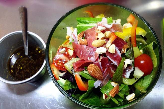 Home Cooking Recipe: Take a large bowl, tear the washed lettuce into the simmer, cut the red and yellow pepper into the squid, put the kiwi fruit into the slice, and cut the small piece of the cherries fruit. Then put the ham on the salad and sprinkle with nuts.