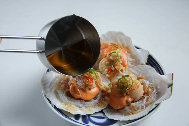 Home Cooking Recipe: Take out, put the green onion on the scallops, and pour a little seafood sauce. Wash the wok and heat it, add 1 tablespoon of the ancient method of peanut oil, and heat the oil evenly on each scallop.