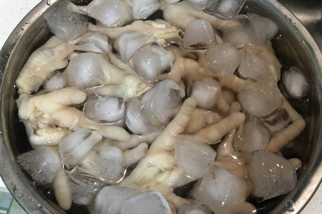 Home Cooking Recipe: The cooked chicken feet are rinsed with cold water, showered, soaked in pre-prepared ice water, covered with plastic wrap and placed in the refrigerator for about one hour.