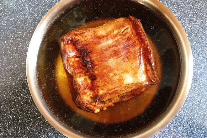 Home Cooking Recipe: The fried pork skin is picked up and placed in a basin filled with water.