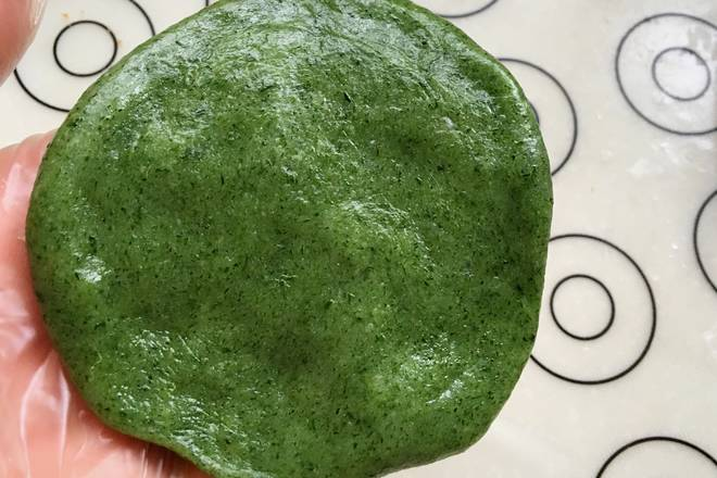 Home Cooking Recipe: The green dough is divided into 12 parts, and a green group skin is rounded and flattened, and it is kneaded into a thin and thick green skin around the middle.