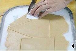 Home Cooking Recipe: The loose dough was placed on a chopping board and rolled into a thin sheet of about 0.3 cm thick. (If the board is not big enough, you can divide the dough into small portions and divide them into pieces.) Place the cut paper model on the patch and cut the pattern with the knife at the edge of the model