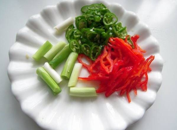 Home Cooking Recipe: The petals of the beans are cut into pieces, and the green peppers are washed. The green onions are cut into sections, and the green and red peppers are shredded separately.