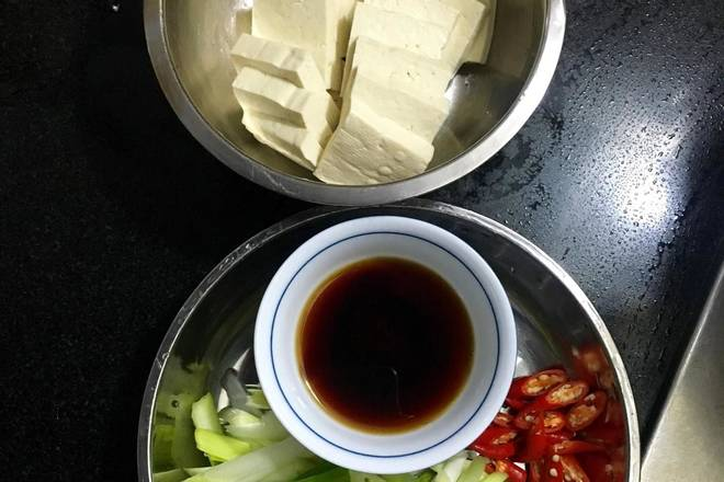 Home Cooking Recipe: The tofu is cut into square pieces about one centimeter thick, the green garlic seedlings are beveled, the millet is spicy and obliquely cut, and the juice is mixed with soy sauce, sugar, oyster sauce and a little water to make the juice;