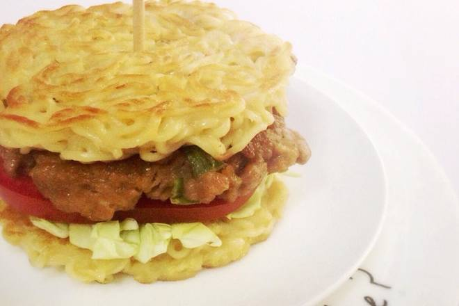 Home Cooking Recipe: Then assemble the burger, the lowest layer is covered with instant noodle burger, stacked with vegetables, tomatoes, squeezed with salad dressing, then garnished with meat patties, and finally put another hamburger embryo.