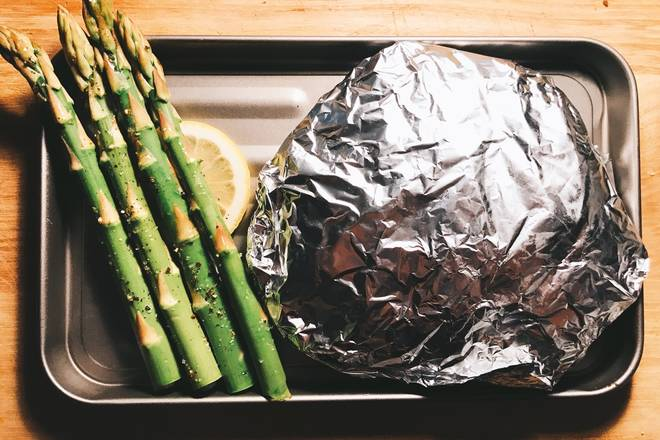 Home Cooking Recipe: They are placed on a baking sheet, and a piece of lemon is placed under the asparagus.