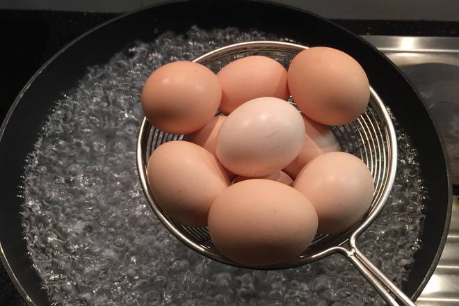 Home Cooking Recipe: Use the sifter to hold the egg into the boiling water, lift it down, and go back and forth 3 times. The egg that pierces the small hole will not burst when it is put into the boiling water.